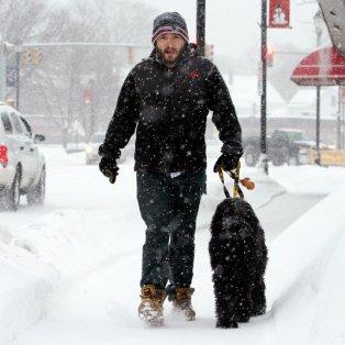 10/02/2015: Στο έλεος του χιονιά και οι ΗΠΑ - Ένα απίθανο στιγμιότυπο με έναν νεαρό να βολτάρει με το σκυλάκι του «τουρτουρίζοντας» από το κρύο! Φωτό: Bill Sikes/AP - Κυρίως Φωτογραφία - Gallery - Video